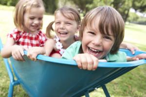 Three Children Sitting In Wheelbarrow